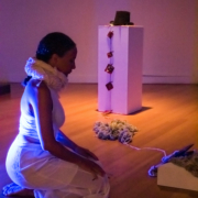 Side view of artist kneeling with stage lighting and art objects in front and in background