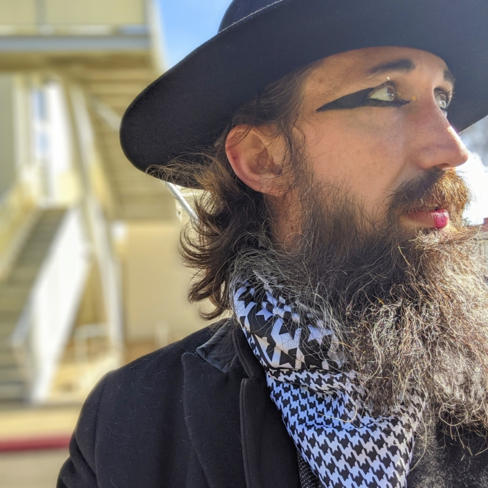 Portrait of Jason long looking to the right, brown hair and beard, wearing hat, stylized eyeliner, patterned scarf, and black jacket